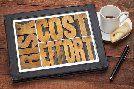 cost, effort, risk - business concept - a word abstract  in vintage wood letterpress printing blocks on a digital tablet with cup of coffee photo