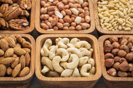 ナッツ要約 - カシュー ナッツ、ピーカン、ヘーゼル ナッツ、木製ボウルでスペインのピーナッツ