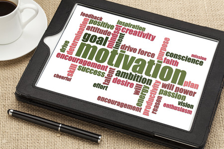 motivation word cloud on a digital tablet with a cup of coffee Banco de Imagens