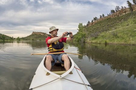 paddler: senior athletic paddler in a  decked expedition canoe photographing on a lake with green vegetation
