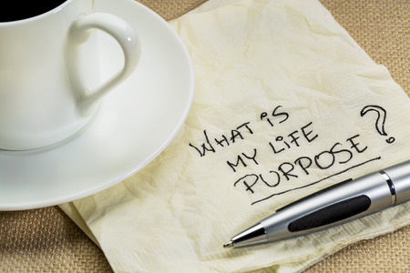 proposito: ¿Cuál es mi propósito en la vida cuestión en una servilleta con una taza de café Foto de archivo