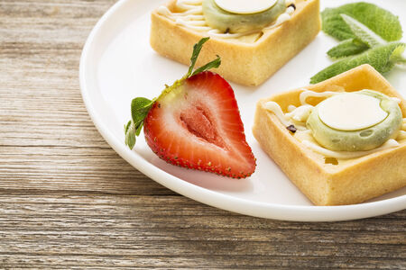 grained: dessert - tarts with strawberry and fresh peppermint on white plate against grained weathered wood, top view
