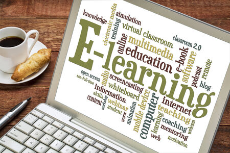 online: online education concept - e-learning word cloud on a laptop with a cup of coffee Stock Photo