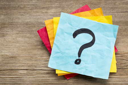 questions: question mark on a sticky note against grained wood
