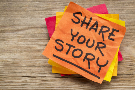 grained: share your story suggestion on a sticky note against grained wood Stock Photo