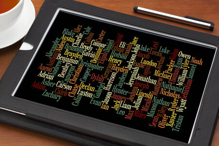 most popular boy baby names in 2012 in USA  - word cloud on a  digital tablet with a cup of tea Stock Photo