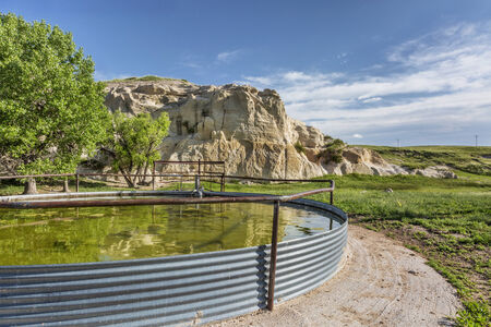 pawnee grassland: cattle water tank and rock cliff,  Pawnee Grassland in northern Colorado Stock Photo