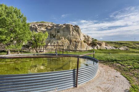 dep�sito agua: tanque de agua el ganado y el acantilado de roca, Pawnee pastizales en el norte de Colorado Foto de archivo