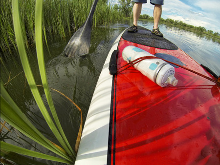 paddleboard: stand up paddling detail, a distorted wide angle view of a paddleboard near lake shore Stock Photo