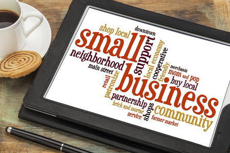 small business: small business word cloud on a digital tablet with a cup of coffee