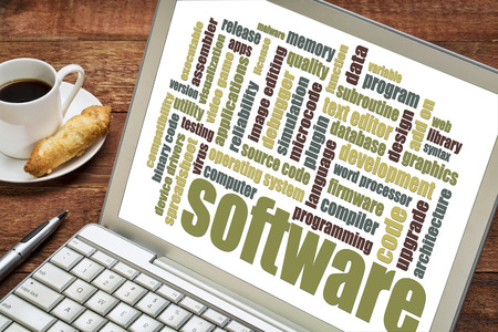 computer simulation: software word cloud on a laptop with a cup of coffee