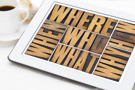 who, what, how, why, where, when, questions  - brainstorming or decision making concept - a collage of words in vintage letterpress wood type on a digital tablet with a cup of coffee photo
