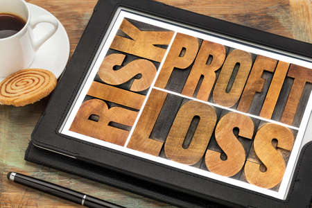 business or investment concept - risk, profit, loss abstract text in vintage letterpress wood type on a digital tablet with a cup of coffee photo