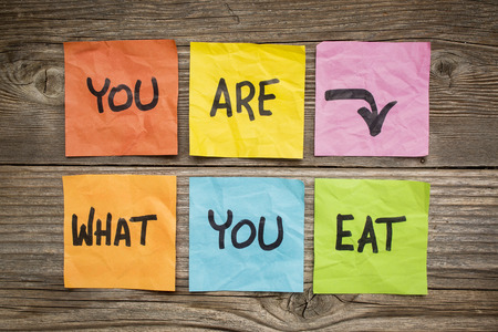 grained: healthy lifestyle concept - you are what to eat reminder words handwritten of colorful sticky notes against grained wood