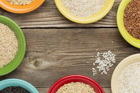 Una variedad de granos de arroz en cuencos de cerámica de colores sobre un rústico de madera, copia espacio Foto de archivo - 29300990