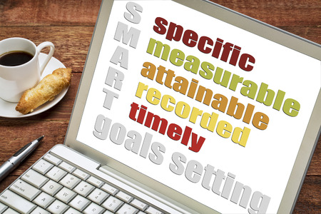 specific: SMART  specific, measurable, attainable recorded, timely  goal setting concept  on a laptop  computer with  espresso coffee