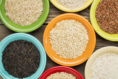 grained: a variety of rice grains on colorful ceramic bowls against a grained wood Stock Photo