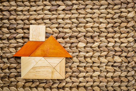 abstract picture of a house built from seven tangram wooden pieces, a traditional Chinese puzzle game, against woven water hyacinth mat, the artwork copyright by the photographer photo