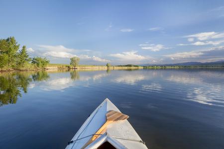 piragua: arco canoa cubierta con un remo en un lago en calma - Lonetree embalse cerca de Loveland, Colorado
