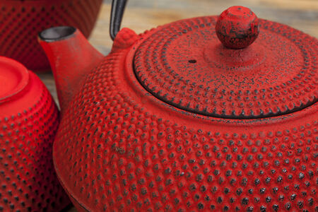 japenese: red tetsubin with tea cups - a detail of a traditional cast iron Japenese teapot Stock Photo