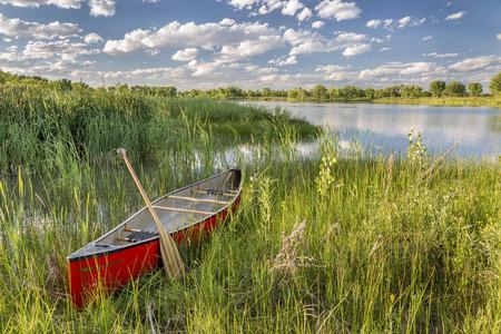rode kano met een houten peddel op de oever van het meer met groene vegetatie Stockfoto