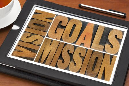 goals, vision and mission - a collage of isolated words in letterpress wood type on a digital tablet with cup of tea Zdjęcie Seryjne