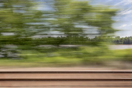 window view: blurry abstract landscape of rail tracks and a river seen from train window in motion
