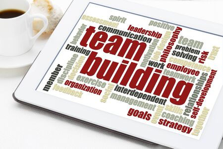team building word cloud on a digital tablet with a cup of coffee