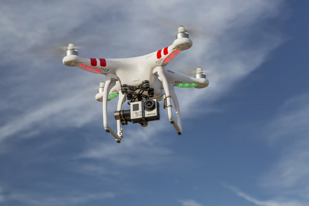 phantom: FORT COLLINS, CO, USA, JULY 24, 2014:  Airborne radio controlled DJI Phantom quadcopter drone with GoPro Hero 3  camera  on a gimbal mount.