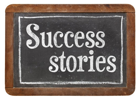success stories - text  with white chalk on a vintage blackboard, isolated on white