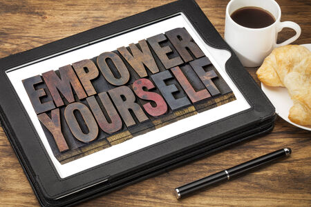 yourself: empower yourself - motivation concept - text in vintage letterpress wood type blocks stained by ink on a digital tablet with cup of coffee Stock Photo