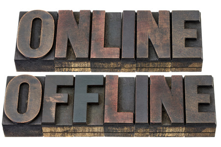 patina: online and offline - internet concept - isolated words in vintage letterpress wood type with ink patina Stock Photo