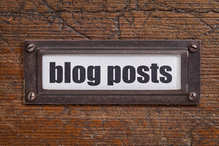 articles: blog posts   tag - file cabinet label, bronze holder against grunge and scratched wood -internet publishing concept Stock Photo