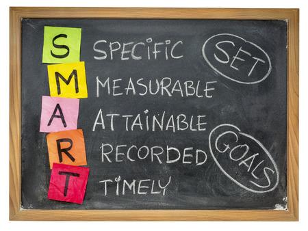 スマート (特定、測定可能、達成可能、記録された、タイムリーな) カラフルな付箋の目標を設定し、チョークを黒板に手書き