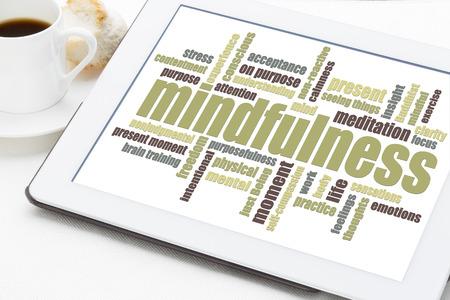 mindfulness: mindfulness woord wolk op een digitale tablet met een kopje koffie
