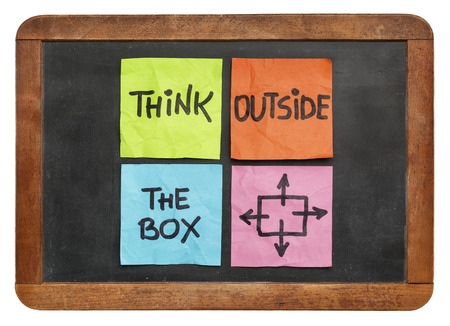 unorthodox: think outside the box concept - colorful sticky notes on a vintage slate blackboard  isolated on white Stock Photo
