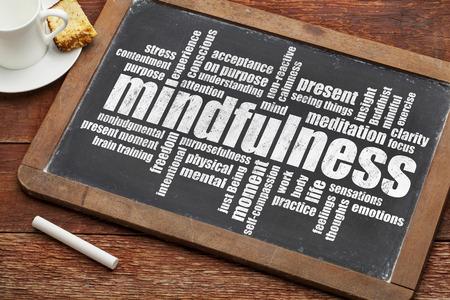 mindfulness woord wolk op een vintage lei schoolbord met een kopje koffie en koekje