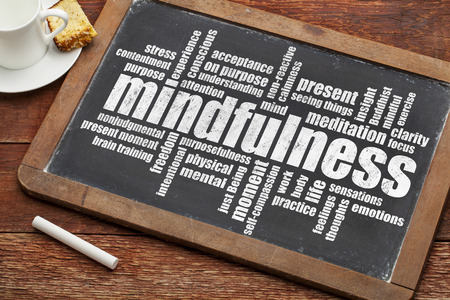 mindfulness word cloud on a vintage slate blackboard with a cup of coffee and cookie Stok Fotoğraf