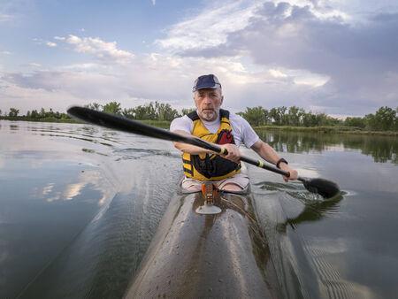 bateau de course: principal masculin pagaie course en kayak de mer sur un lac calme avec des nuages ??d'orage en arrière-plan, Fort Collins, Colorado
