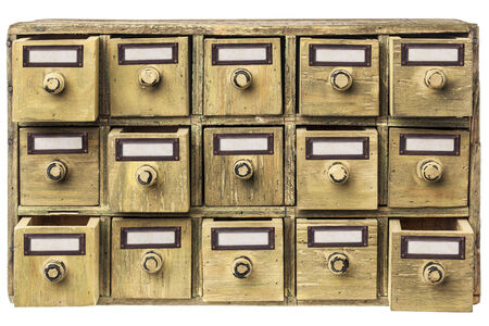 drawers: primitive wooden apothecary or catalog cabinet with partially open drawers and blank labels in bronze holders