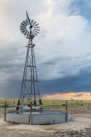 pawnee grassland: windmill with a pump and cattle water tank in shortgrass prairie against stormy sky, iPawnee National Grassland in Colorado near Grover