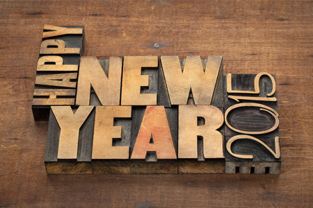 Happy New Year 2015 greetings  - text in vintage letterpress wood type blocks on a grunge wooden background photo