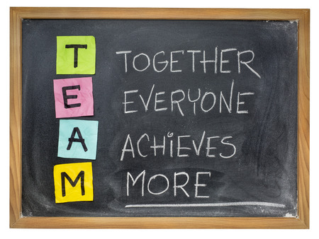 white achievement: TEAM acronym (together everyone achieves more), teamwork motivation concept, color sticky notes, white chalk handwriting on blackboard