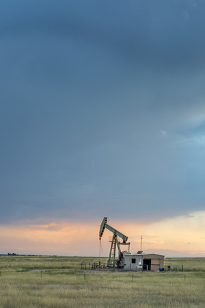pawnee grassland: oil rug (pumpjack) against stormy sunset sky in Pawnee National Grassland near Grover, Colorado Stock Photo
