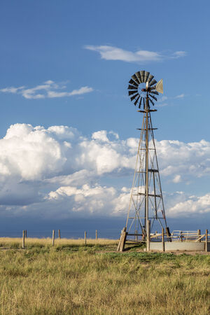 pawnee grassland: windmill with a pump and cattle water tank in shortgrass prairie against stormy sky, Pawnee National Grassland in Colorado near Grover