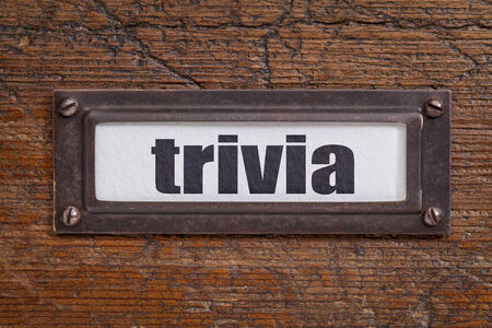 trivia: trivia - file cabinet label, bronze holder against grunge and scratched wood
