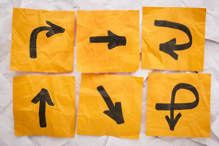 Verwarrende richtingen concept - een verscheidenheid van pijlen op verfrommeld, oranje memoblokjes Stockfoto - 30898010