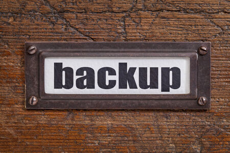 data recovery: backup - file cabinet label, bronze holder against grunge and scratched wood