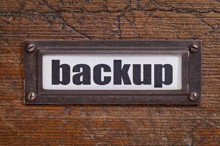 deletion: backup - file cabinet label, bronze holder against grunge and scratched wood