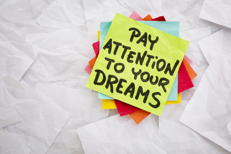 pay attention to your dreams  - reminder or advice handwritten on a colorful sticky note Imagens